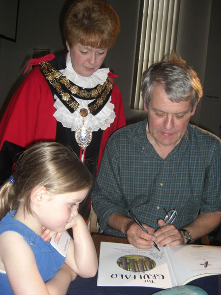 "Mayor Cllr Jane Boulton looks on as Axel Scheffler signs Amber Willcox's copy of ""The Gruffalo"""